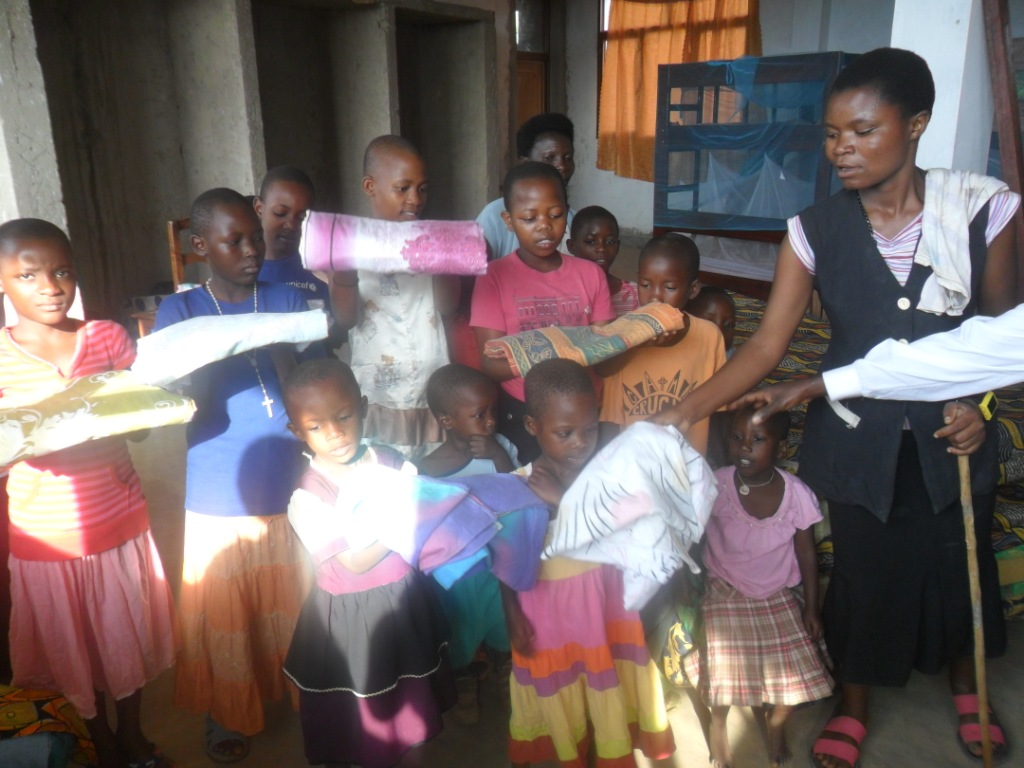 De kinderen van het weeshuis in Burundi tonen de lakens die ze net hebben gekregen.
